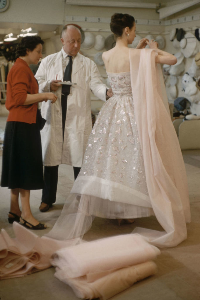 Christian Dior in the salon with a model | Image: Getty