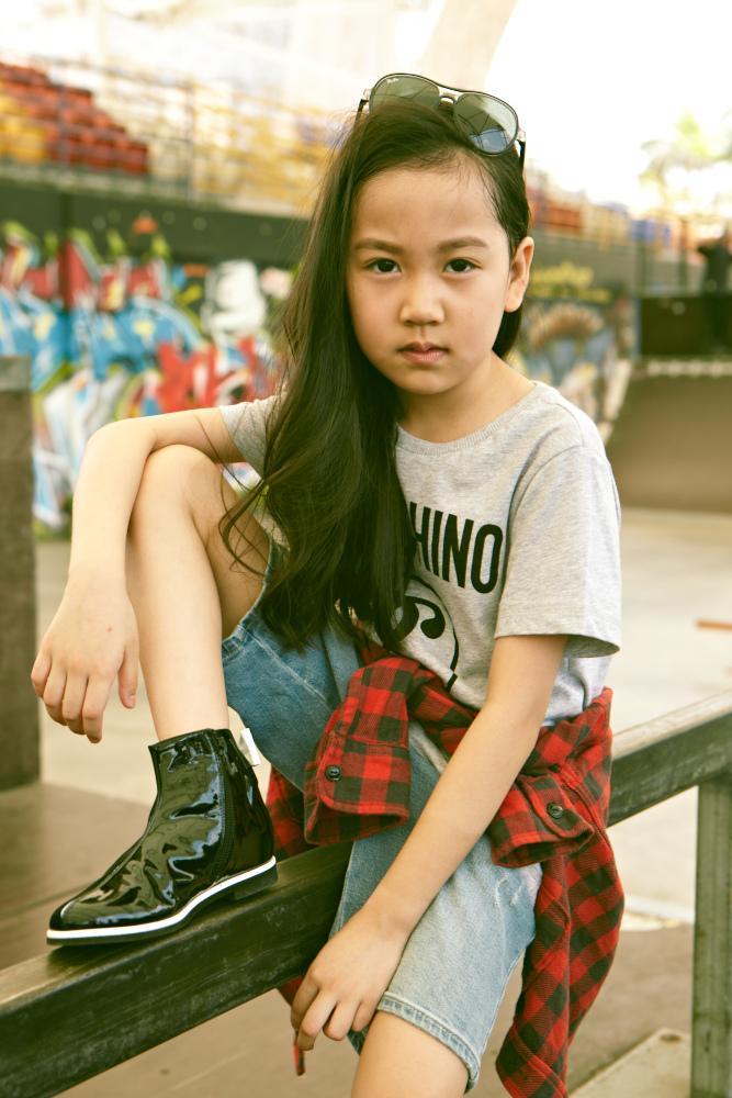 Gabryelle Tang: Shirt, Moschino Kids. Flanner shirt (worn around waist), Zara Kids. Denim shorts, Armani Junior, Patent boots, Baby Dior, Sunglasses, Ray-Ban.