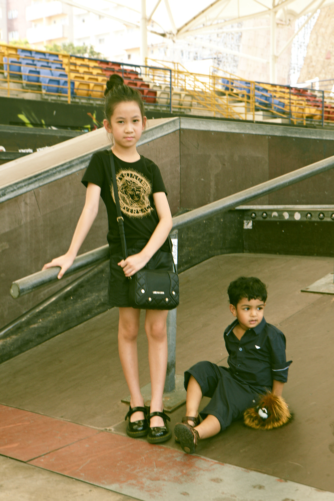 Gyzelle Tang (L): Bomber jacket, Armani Junior. Shirt, Young Versace. Leather skirt and Mary Janes, both model's own. Bag, Love Moschino. Leo Siva (R): Shirt, Armani Junior. Shorts, Paul Smith Junior. Charm, Fendi. Shoes, model's own.