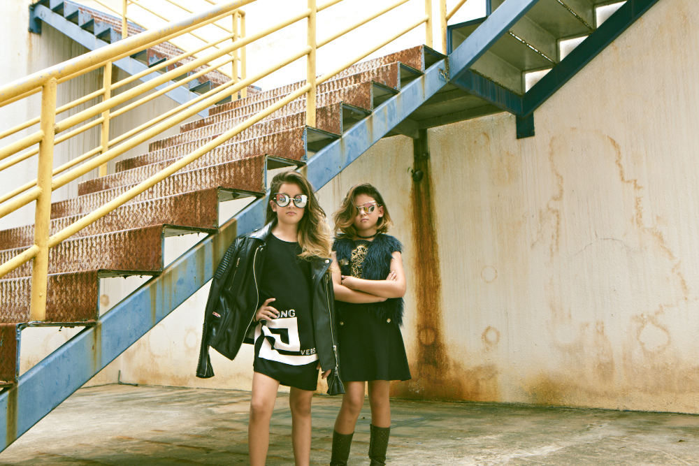 Keia Lo (L): Leather jacket, Burberry Brit. Shirt (worn as dress), Young Versace. Sunglasses, model's own. Elie Lo (R): Dress, Young Versace. Gilet; sunglasses; and choker, all model's own.