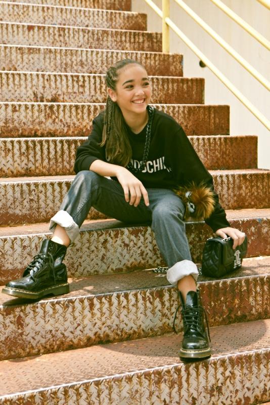 Sofia Landis: Sweater, Love Moschino. Boyfriend jeans, Jean Paul Gaultier Kids. Bag, Moschino. Charm, Fendi. Boots, Dr. Martens.