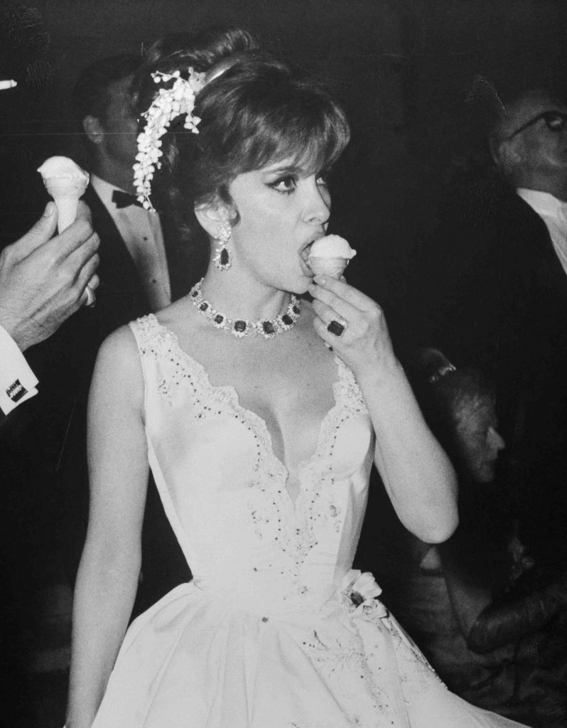 10 Jun 1966, Monte Carlo, Monaco --- Original caption: It's always a refreshing sight watching actress Gina Lollobrigida refreshing herself. Here, she munches little-girl style on an ice cream cone at the Monaco Centenary Ball. But as her fashion emphasizes, Gina is no little girl. Indeed. --- Image by © Bettmann/CORBIS