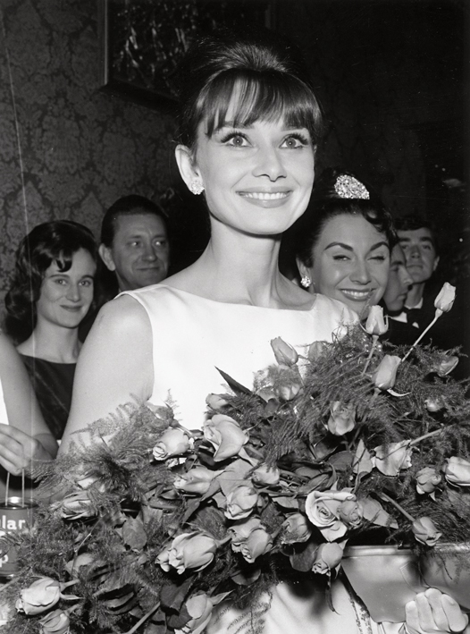 Image: Getty; The ever-graceful Audrey Hepburn with a bouquet of roses in 1965